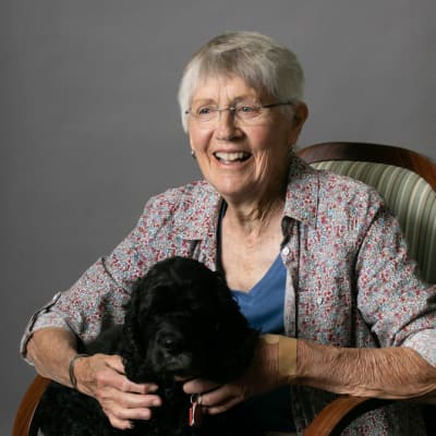 Resident sitting in a chair with her cute black dog at Deephaven Woods in Deephaven, Minnesota