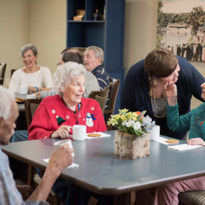 Group of residents sitting at a table ordering food at Deephaven Woods in Deephaven, Minnesota