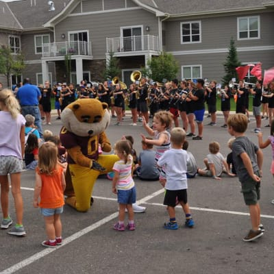 Kids interacting with a sports mascot outside at an intergenerational activity held by Deephaven Woods in Deephaven, Minnesota