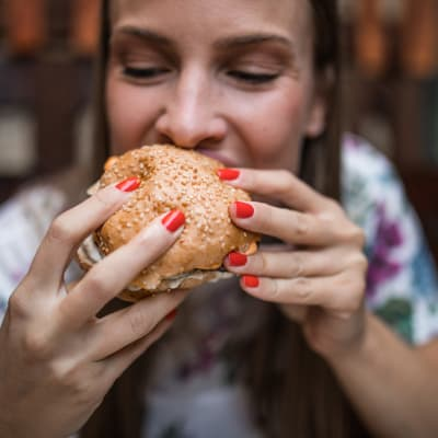 Resident enjoying a burger from a local restaurant near The Acadian Apartment Homes in Maurice, Louisiana