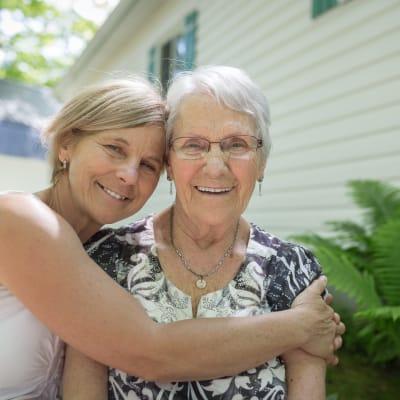 Caretaker hugging a resident outside at Deer Crest Senior Living in Red Wing, Minnesota