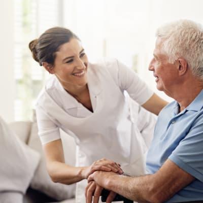 Caretaker talking to a seated resident at York Gardens in Edina, Minnesota