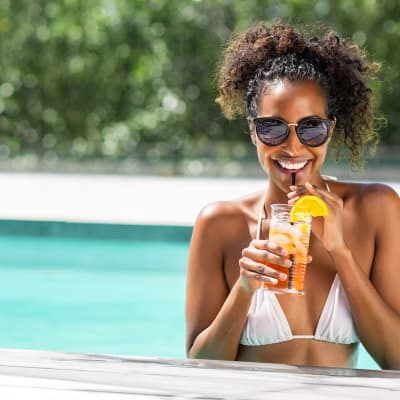 Resident enjoying a drink in the refreshing swimming pool at The Reserve at White Oak in Garner, North Carolina