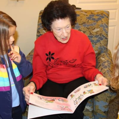 Resident reading a book with a child at Aurora on France in Edina, Minnesota