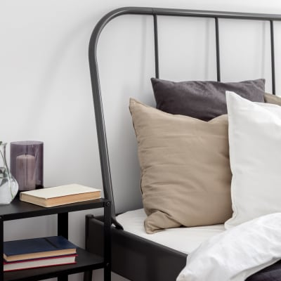 Bed with multiple pillows and side table with books at Marquis at Buckhead in Atlanta, Georgia