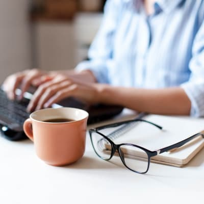 Resident working from home with coffee mug, glasses, and notebook on desk at Marq Eight in Atlanta, Georgia