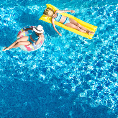 Two residents floating pool on pool raft and innertube at Marq on Burnet in Austin, Texas