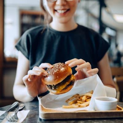 Resident eating a burger near Bellrock Summer Street in Houston, Texas