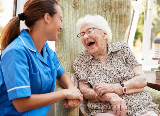 Staff nurse and resident share a joke at Westminster Memory Care in Aiken, South Carolina
