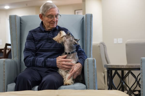 Senior having fun with his pet at Iris Memory Care of Edmond
