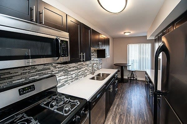 Interior view of kitchen amenities at Spice Tree Apartments including hardwood flooring and stainless steel appliances