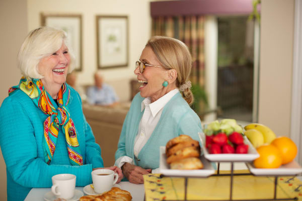 Two residents laughing over a cup of coffee and some fruit and pastries at Discovery Senior Living in Bonita Springs, Florida