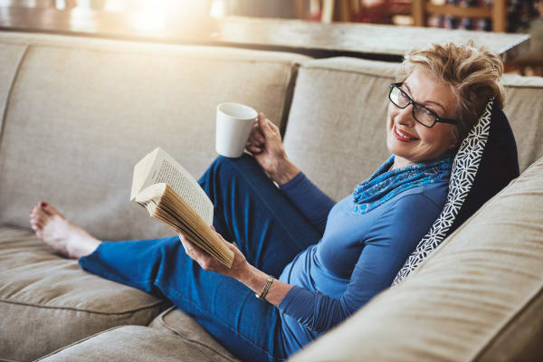 Woman enjoying coffee on the couch at Park Row Senior Apartments in Bowling Green