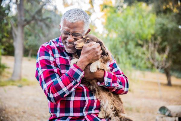 A man hugs his pup near Park Row Senior Apartments in Bowling Green