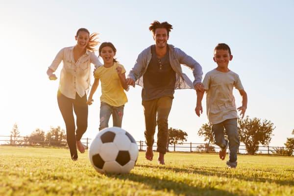 Family playing soccer in a field near Villa del Rio Apartments in Sacramento, CA