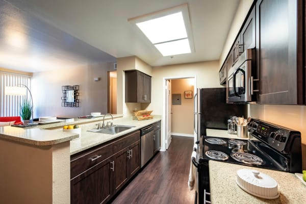 Brown renovation kitchen with Stainless steel appliances at Sierra Del Oro Apartments in Corona,
