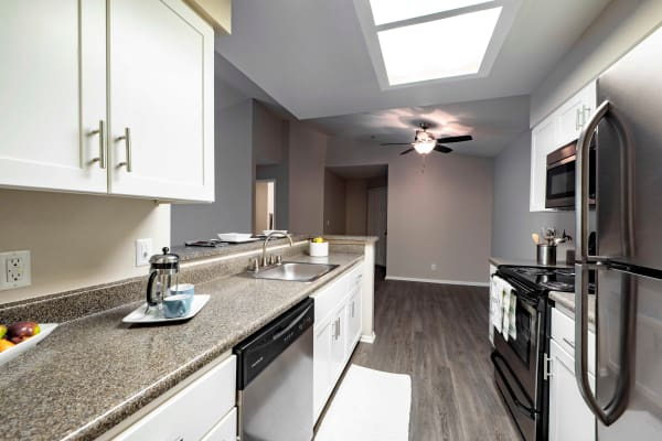 White renovated kitchen with Stainless steel appliances at Sierra Del Oro Apartments in Corona