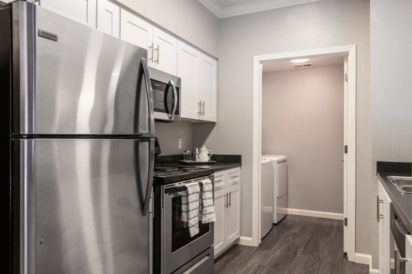 White renovated kitchen with stainless steel appliances at Hawthorn Village Apartments in Napa,