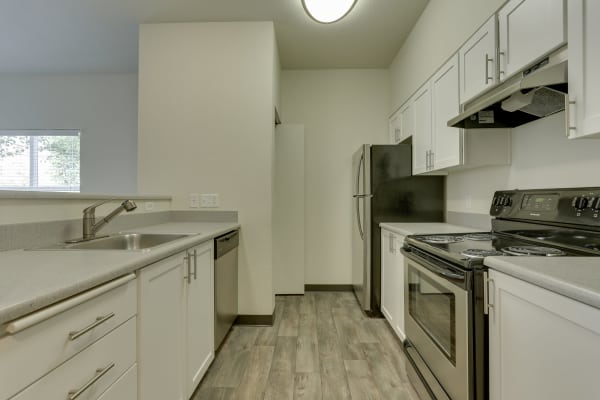 Fully equipped kitchen with stainless steel appliances at The Landings at Morrison Apartments in Gresham