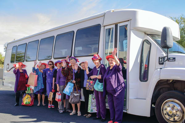 Residents waving in front of the community bus at Alexis Estates Gracious Retirement Living in Allen, Texas