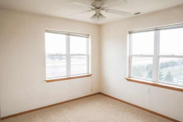 Apartment bedroom with two windows at West Towne in Ames, Iowa