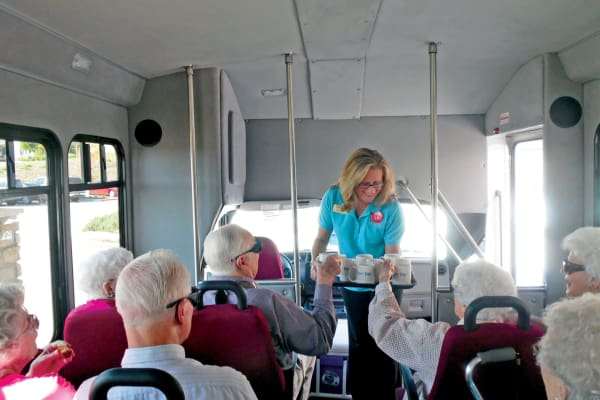 Residents being handed mugs on the bus at Meadowlark Estates Gracious Retirement Living in Lawrence, Kansas