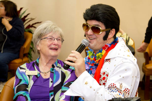 A resident enjoying listening to an Elvis impersonator sing at Cottonwood Estates Gracious Retirement Living in Alpharetta, Georgia