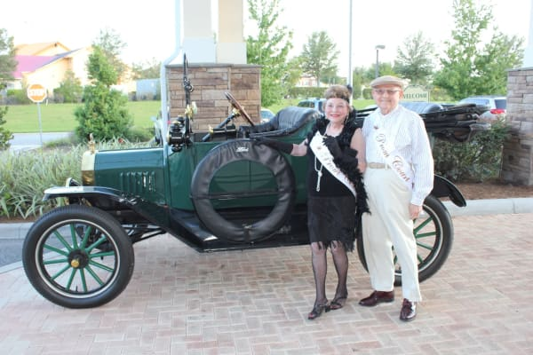 Two residents dressed for prom in front of a classic car at Desert Springs Gracious Retirement Living in Oro Valley, Arizona