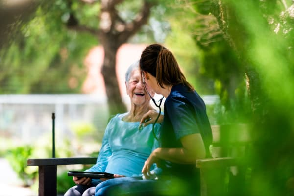 A resident woman and nurse outside in the garden at Peninsula Reflections in Colma, California