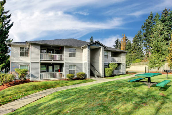 Exterior building View with picnic table and lush landscaping at Pebble Cove Apartments in Renton