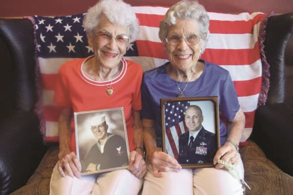 Two residents holding photos at Ivy Creek Gracious Retirement Living in Glen Mills, Pennsylvania