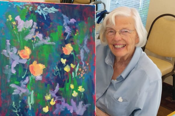 A resident holding her painting at Pioneer Ridge Gracious Retirement Living in McKinney, Texas