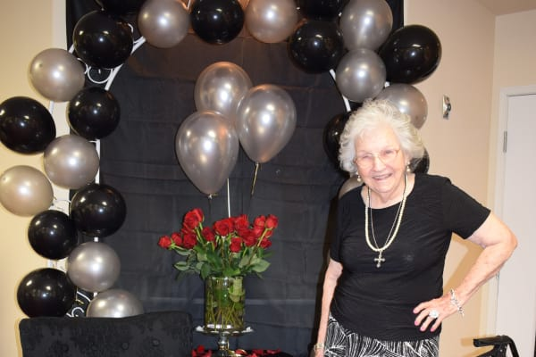 A resident in front of a balloon arch at Pioneer Ridge Gracious Retirement Living in McKinney, Texas