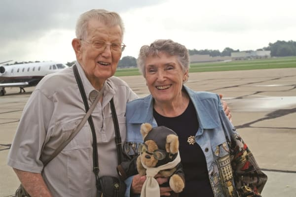 Two residents from Providence Meadows Gracious Retirement Living in Charlotte, North Carolina next to a plane
