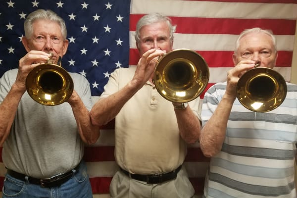Three residents with trumpets at Providence Meadows Gracious Retirement Living in Charlotte, North Carolina