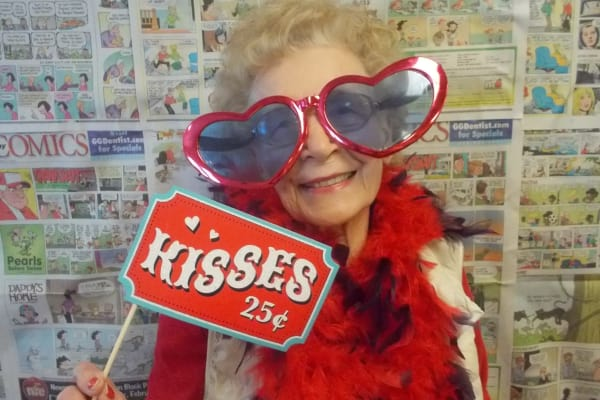 A resident with heart glasses and a kisses twenty-five cents sign at Scholl Canyon Estates in Glendale, California