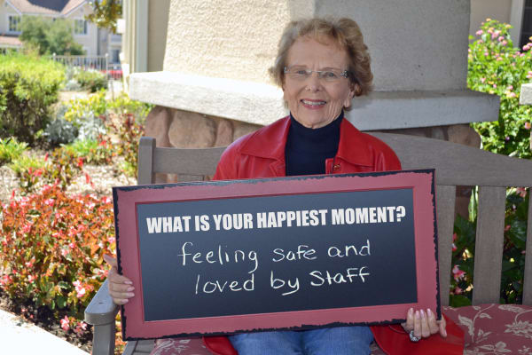 A resident holding a sign with her favorite memory at Somerset Lodge in Gladstone, Oregon