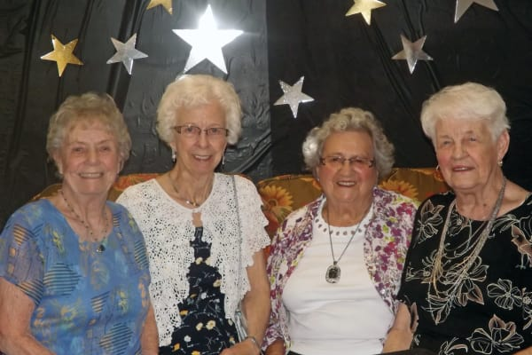 Four residents in front of a backdrop at The Highlands Gracious Retirement Living in Westborough, Massachusetts
