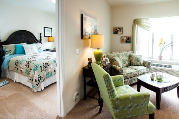 An apartment bedroom and living room at Whispering Pines Gracious Retirement Living in Raleigh, North Carolina