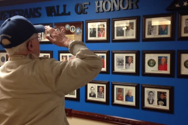 A veteran resident facing the wall of honor at Mulberry Gardens Assisted Living in Munroe Falls, Ohio