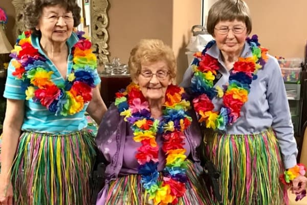 Residents dressed in leis and hula skirts at Mulberry Gardens Memory Care in Munroe Falls, Ohio