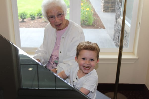A resident playing piano with a young child at Amber Park in Pickerington, Ohio