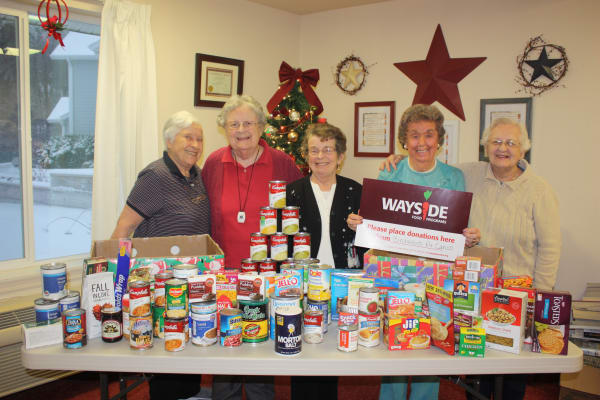 Residents with canned food donations at Birchwoods at Canco Assisted Living in Portland, Maine
