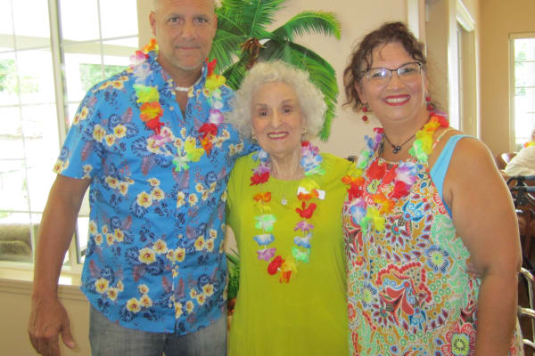 Managers with a resident at Bella Vista Gracious Retirement Living in Asheville, North Carolina enjoying a luau