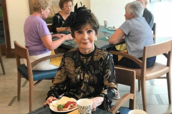 Resident at All Seasons Naples in Naples, Florida having a meal with her tea
