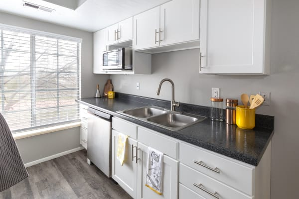 White cabinet renovation with stainless steel appliances at Windgate Apartments in Bountiful, Utah
