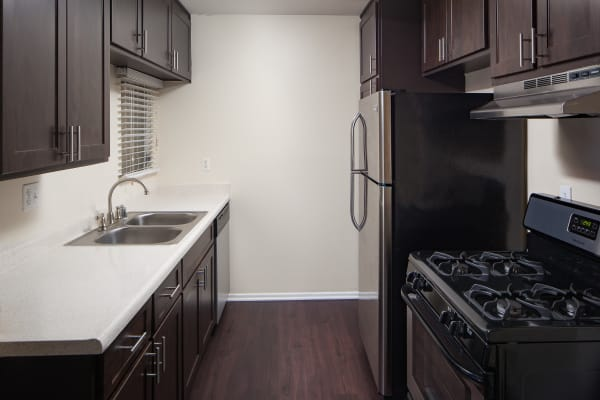 Brown renovated kitchen cabinets with stainless steel appliances at Kendallwood Apartments in Whittier,CA
