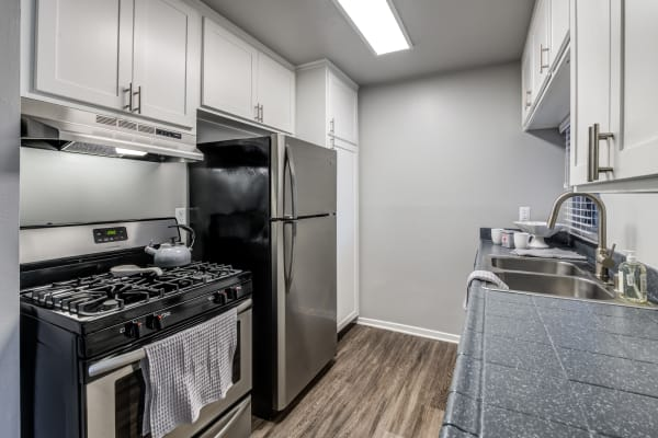 white kitchen cabinetry renovation with stainless steel appliances at Kendallwood Apartments in Whittier