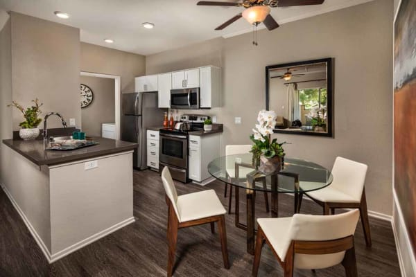 An apartment kitchen and dining room at Colonnade at Sycamore Highlands in Riverside, California
