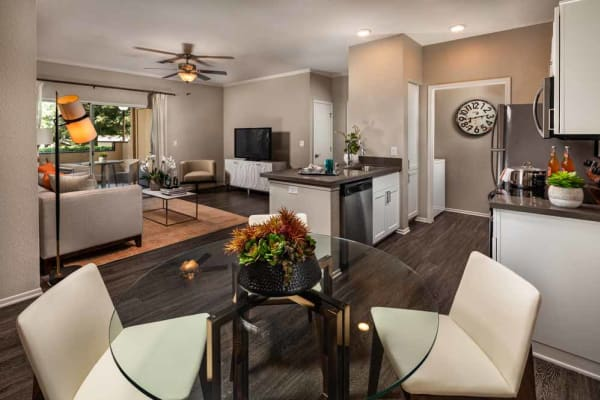 The dining room leads into the apartment living room at Colonnade at Sycamore Highlands in Riverside, California